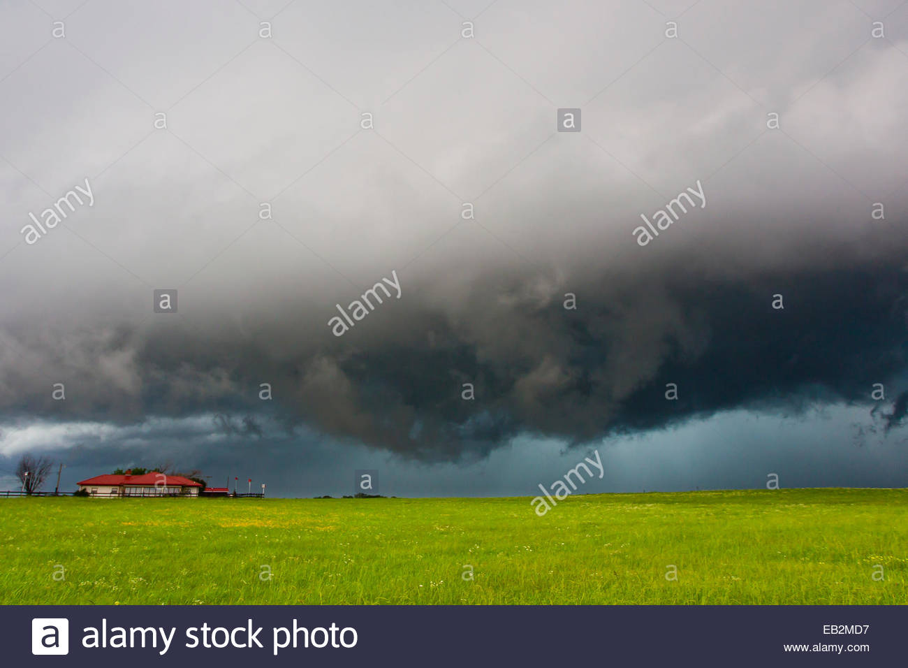 Dark skies from a supercell thunderstorm over a ranch and fields. - Stock Image