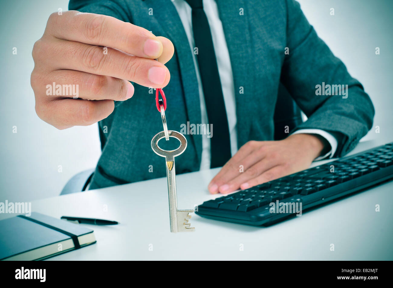 a man in suit sitting in an office desk giving the key to the observer - Stock Image