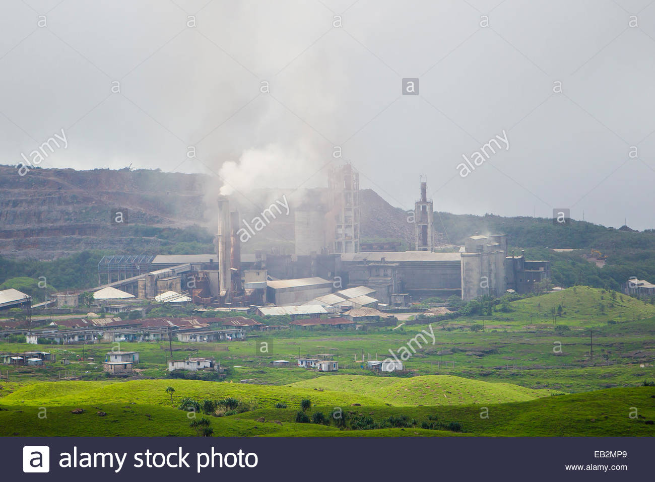 Dust, smoke, and other pollutants rising from and filling the air surrounding the Mawmluh Cement Plant. - Stock Image