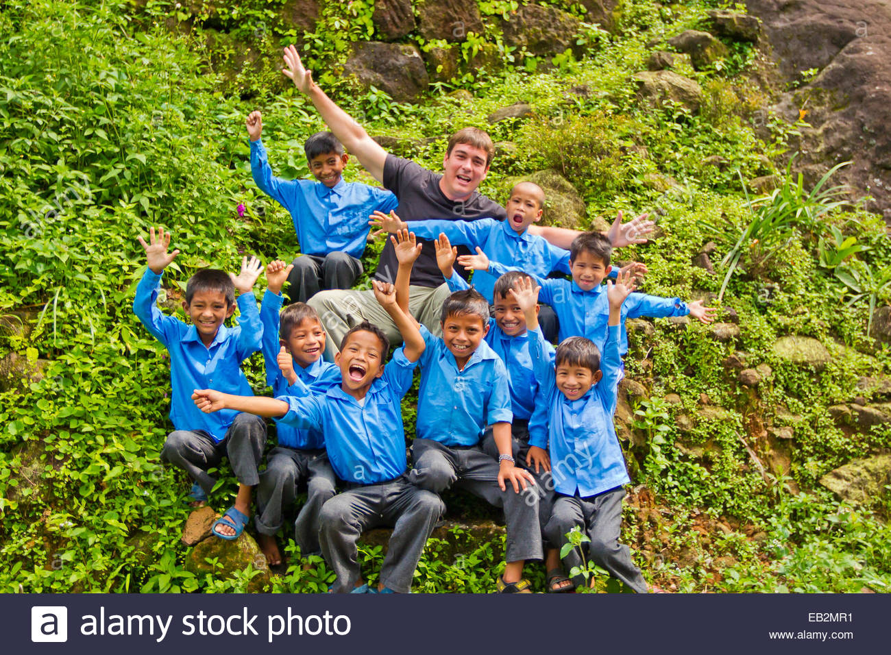 Photographer and weather personality, Mike Theiss, meeting and cutting up with local school boys in a small village. - Stock Image