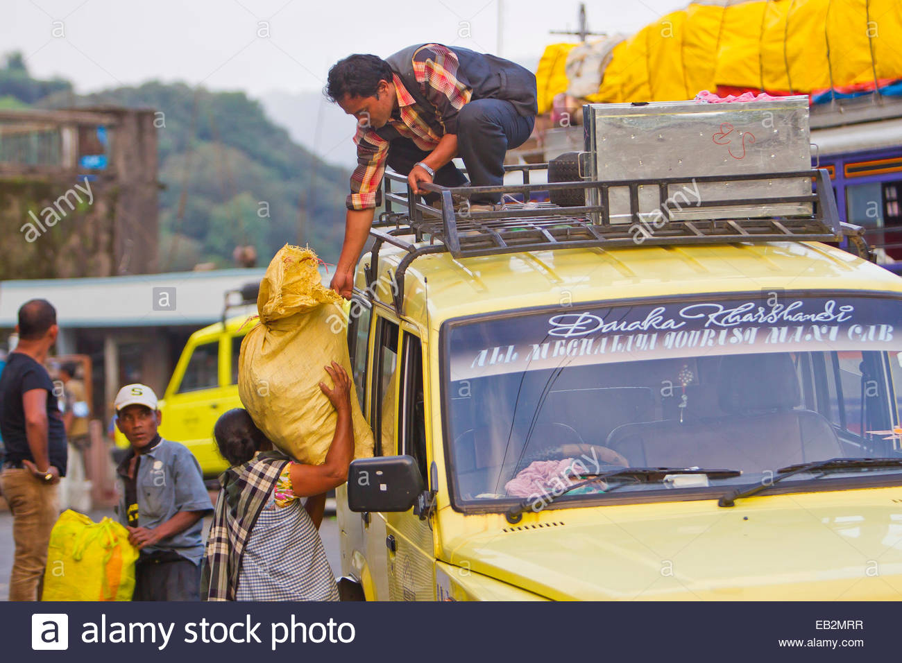 Indian people unloading a truck loaded with supplies. - Stock Image