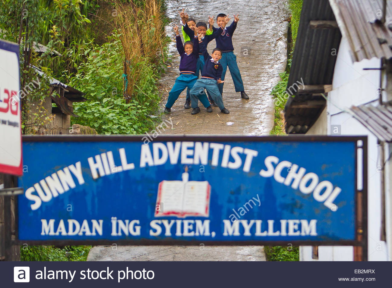 School boys in uniforms cutting up and giving the peace sign in front of their school. - Stock Image