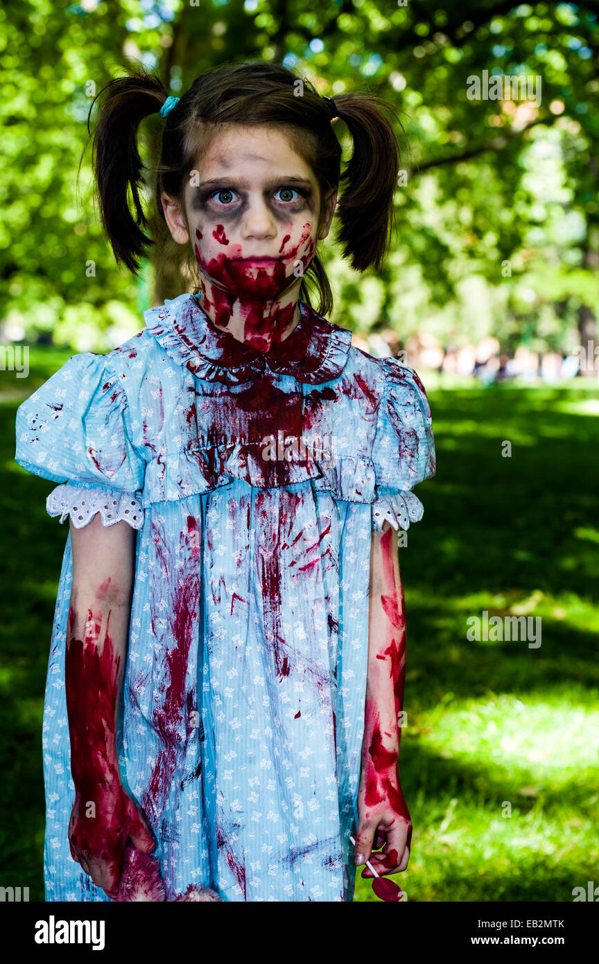 A blood-soaked zombie girl with pigtails in a pretty blue dress at a festival. - Stock Image