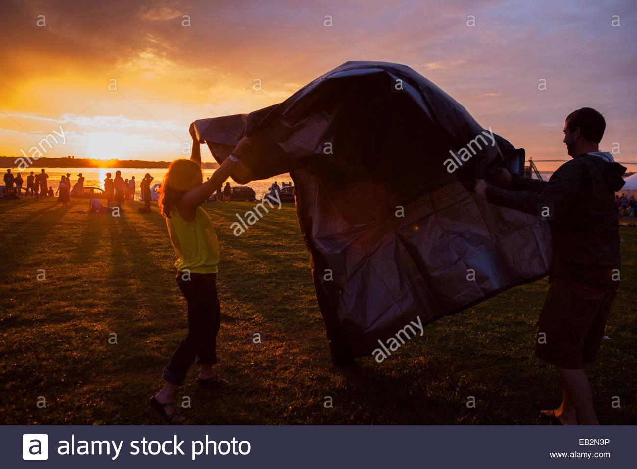Fans folding tarp at sunset at Newport Harbor as folk festival closes - Stock Image