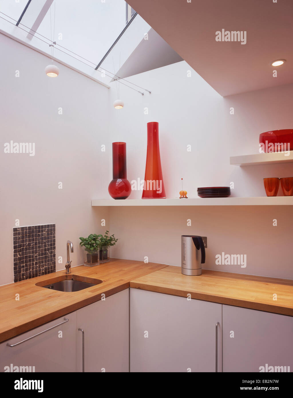 Red glassware on kitchen shelving under skylight in converted Grainstore, Perthshire, Scotland, UK. - Stock Image