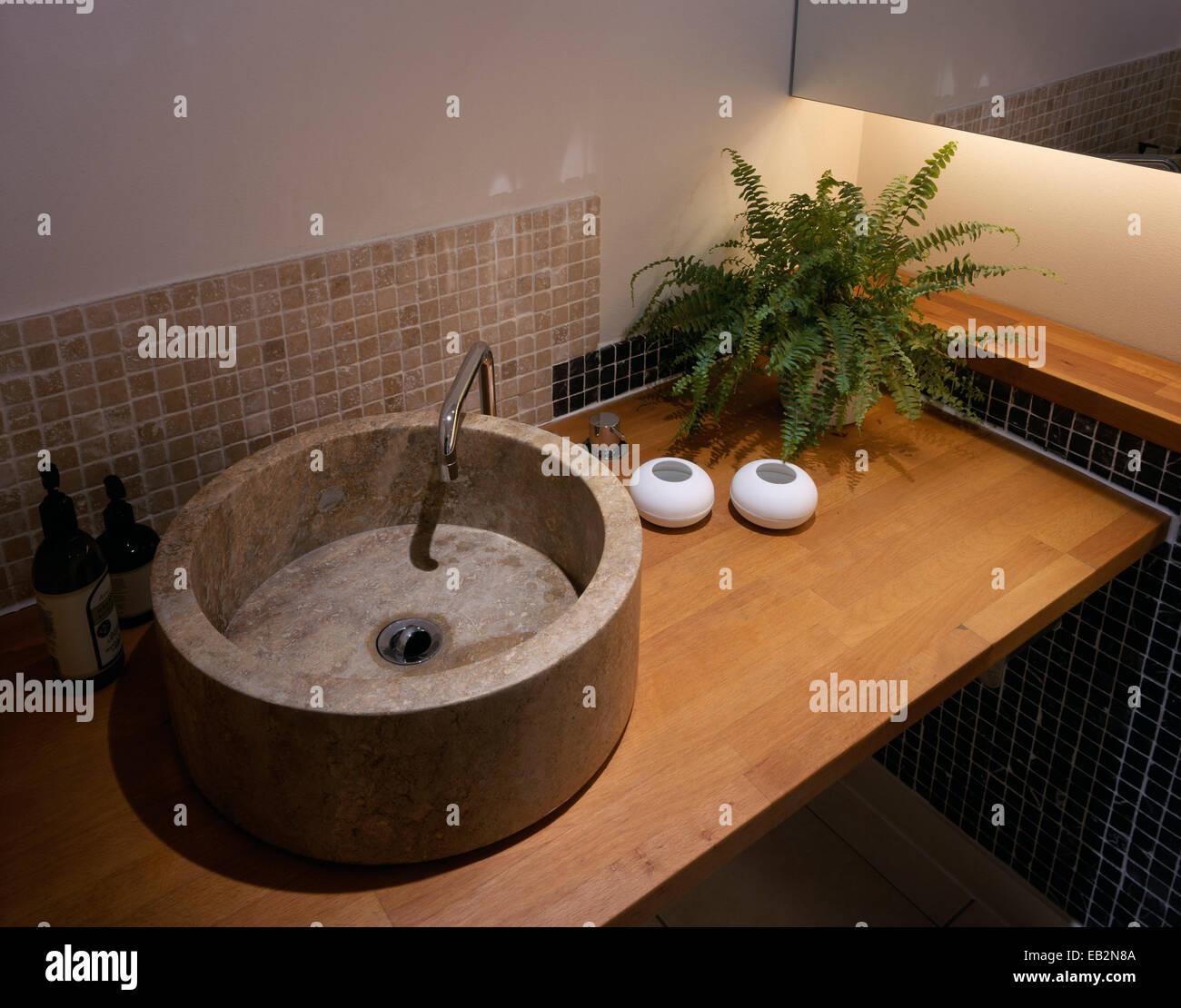 Round stone washbasin in modern bathroom in The Grainstore, Perthshire, Scotland - Stock Image