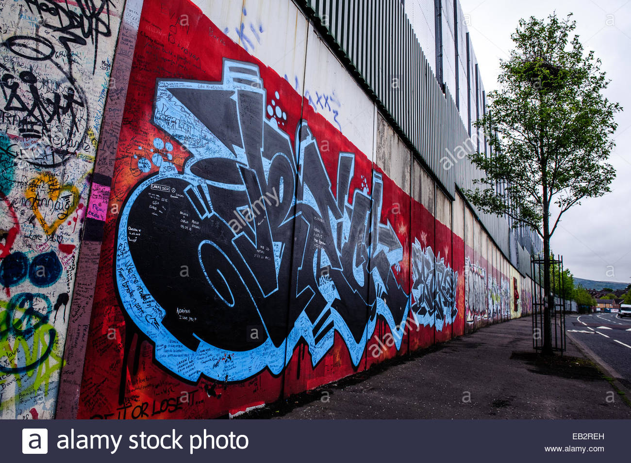 Political graffiti on the Peace Wall in Belfast. - Stock Image