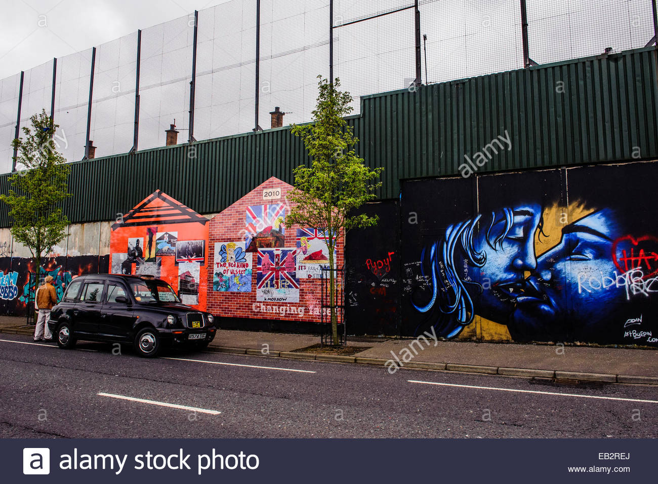 Political murals and graffiti on the Peace Wall in Belfast. - Stock Image
