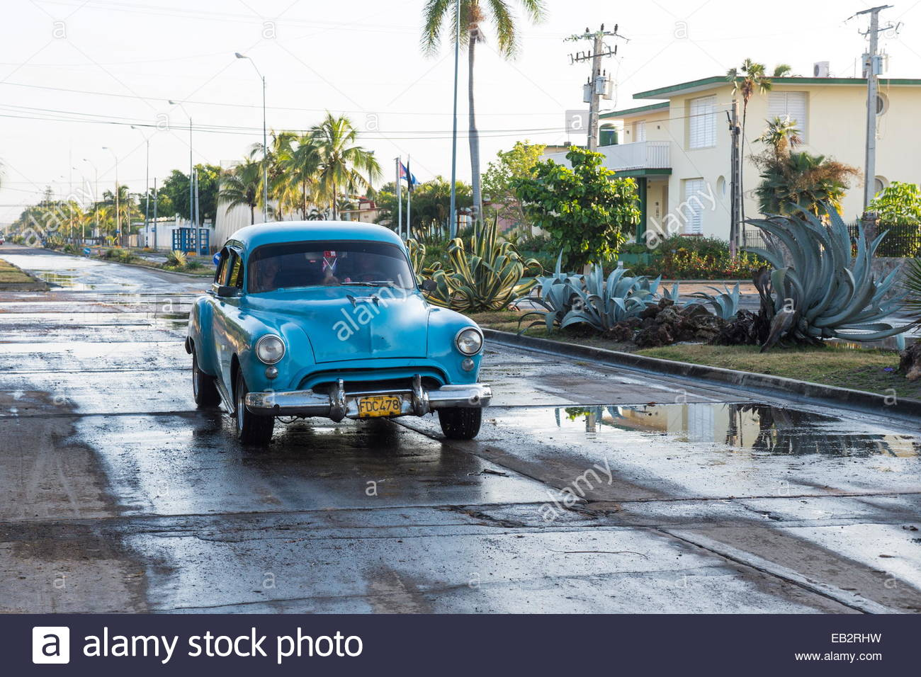 Early morning after a rain storm old cars drive through wet streets in Cienfuegos, Cuba. - Stock Image