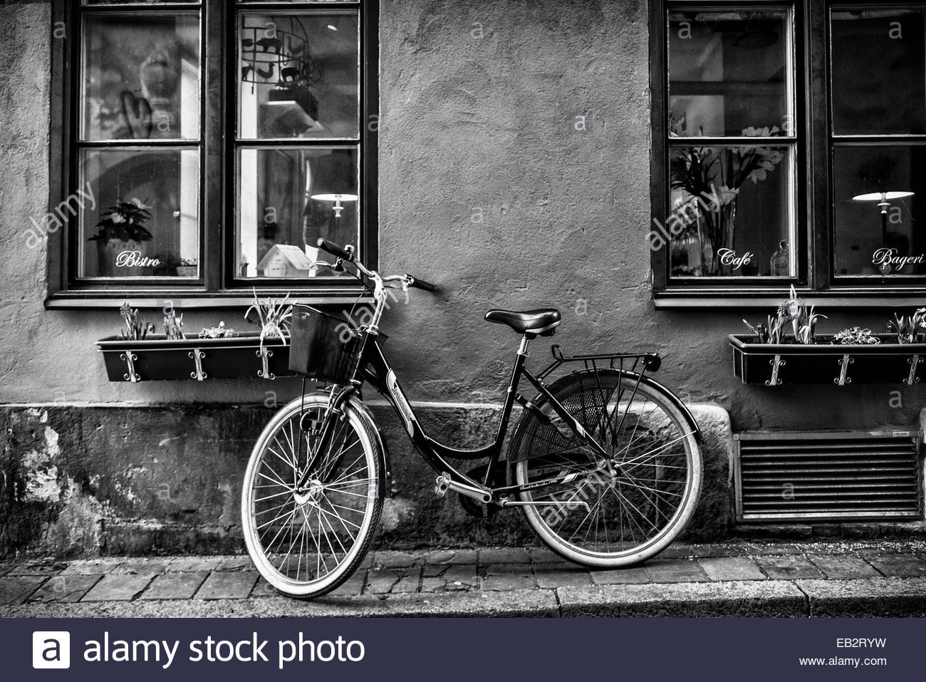 A bicycle parked on a sidewalk below two windows. - Stock Image