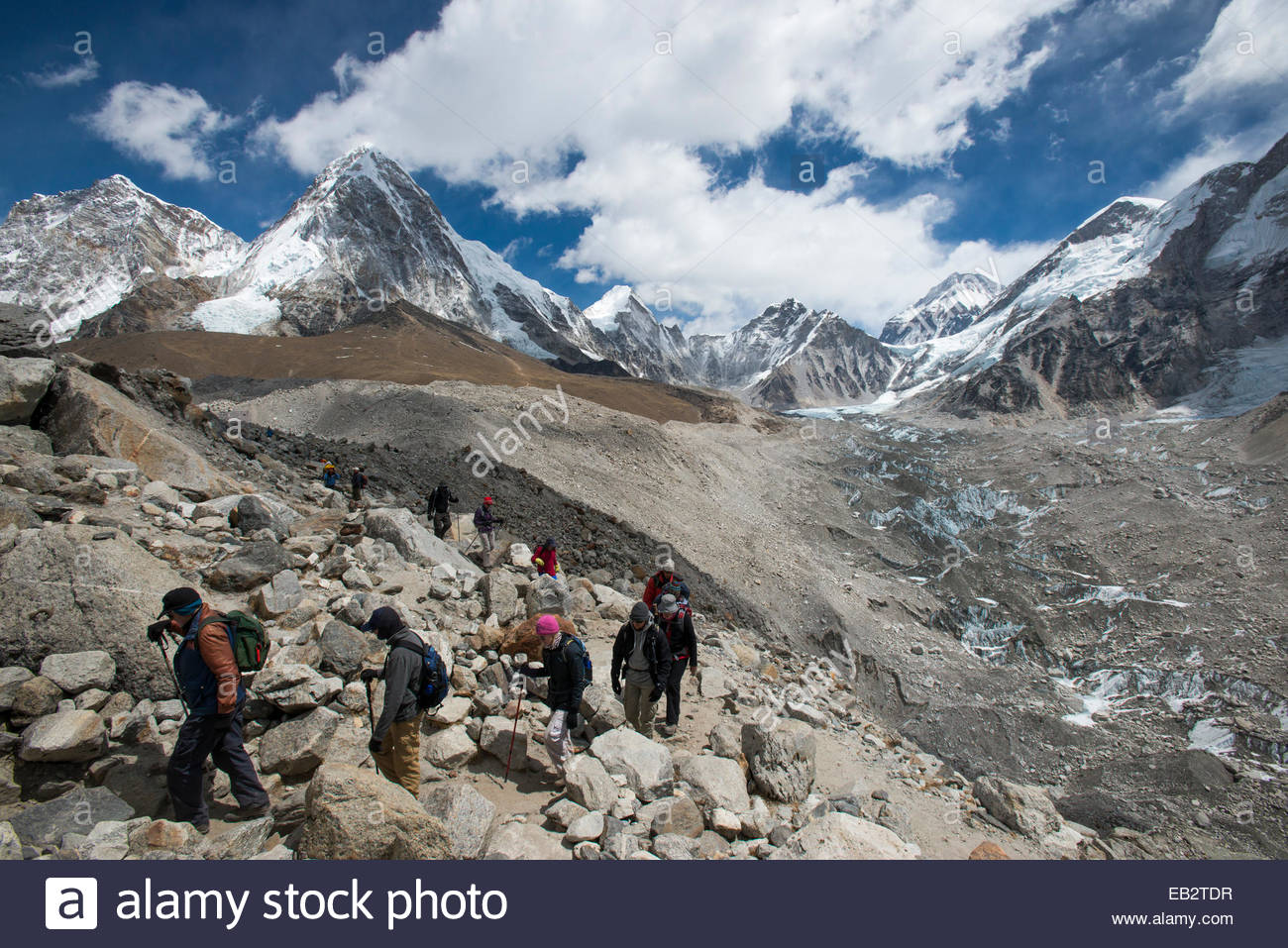 Trekkers make their way down from Everest Base Camp beside the Khumbu glacier in Nepal - Stock Image
