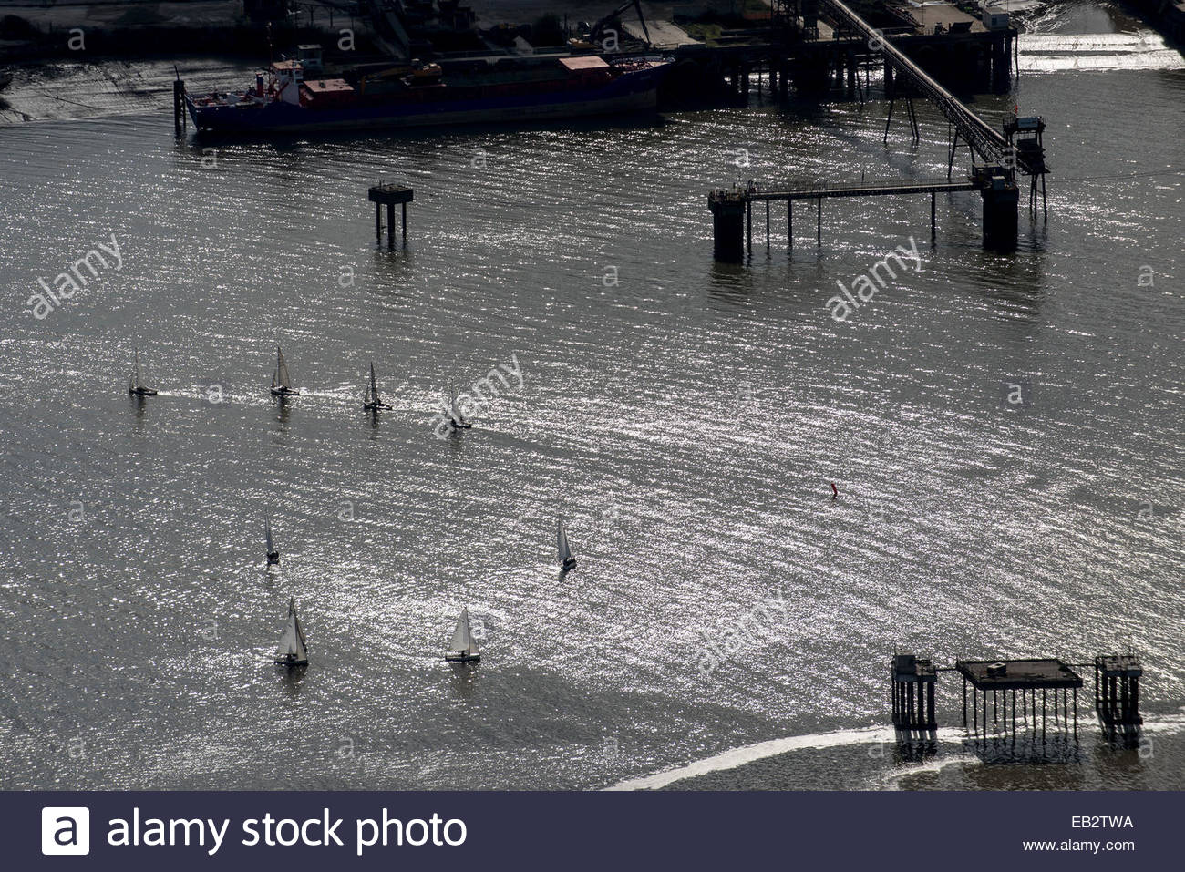 An aerial view of sailing dinghies competing in a race on the Thames river near Docklands - Stock Image