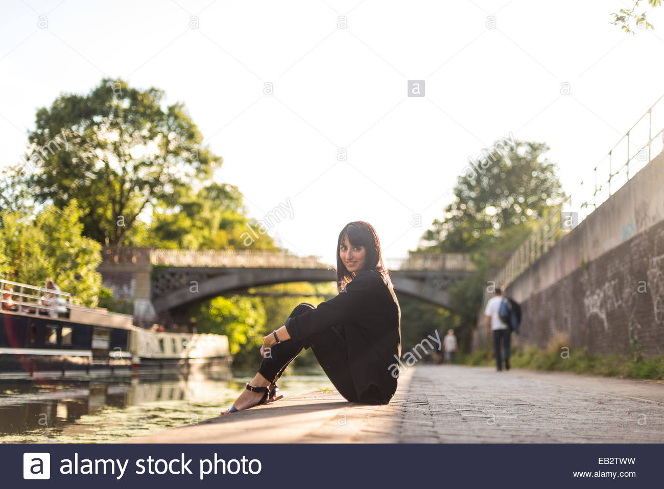 A pretty girl sitting besides Regents Canal in Primrose Hill - Stock Image