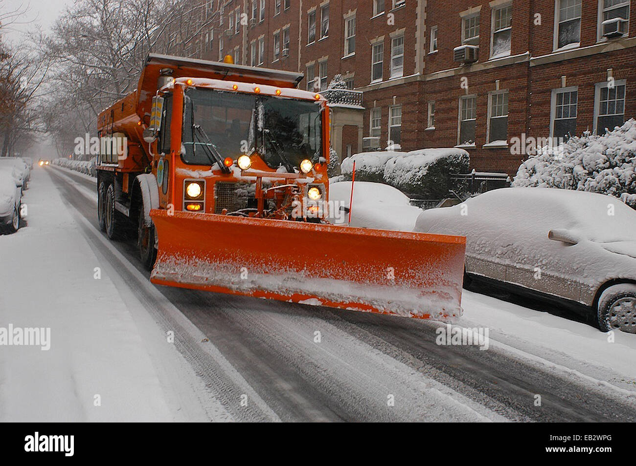 A snow plough passes parked cars in New York City during a blizzard. - Stock Image