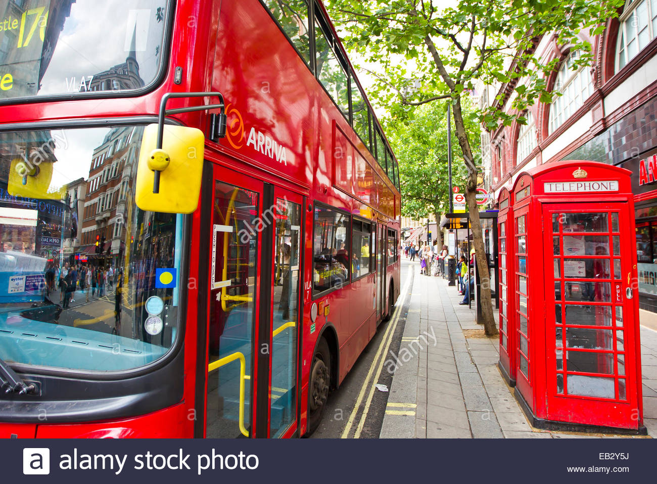 A bright red double decker bus parked next to a pair of iconic red phone booths. - Stock Image