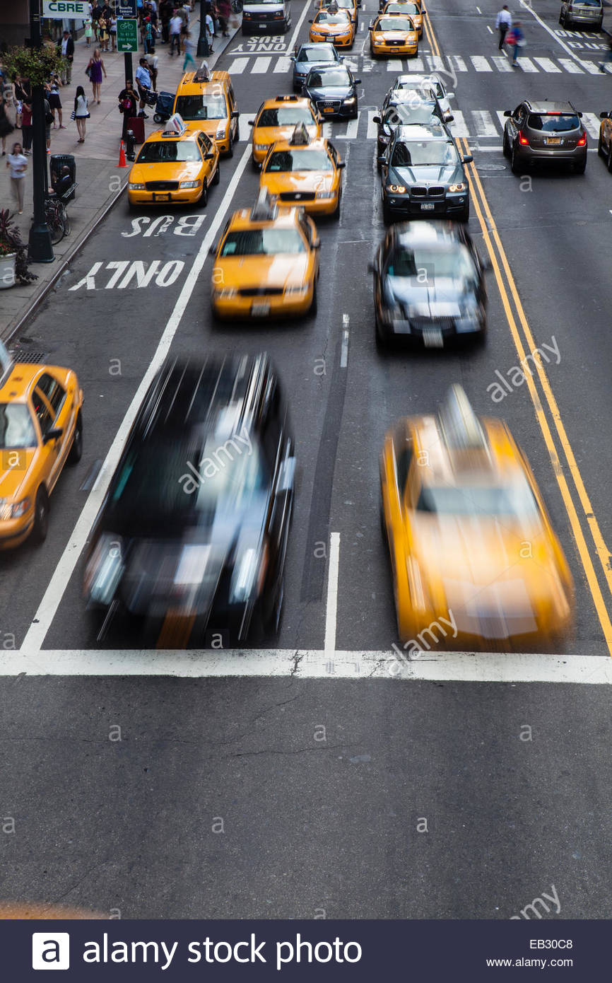 Taxi cabs race across 42nd Street in Manhattan - Stock Image