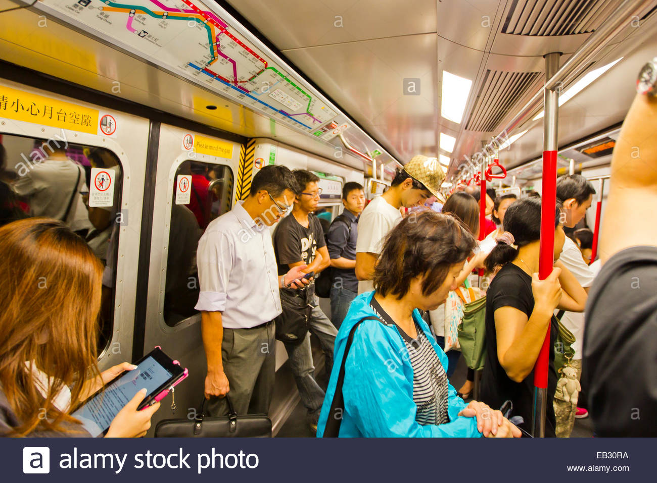 Travelers immersed in smart phones and other technology while riding the Hong Kong subway. - Stock Image