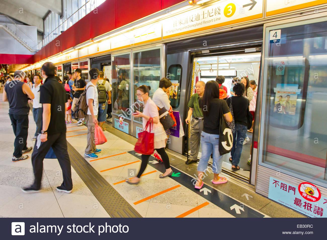 Travelers getting off at a subway station in Hong Kong. - Stock Image