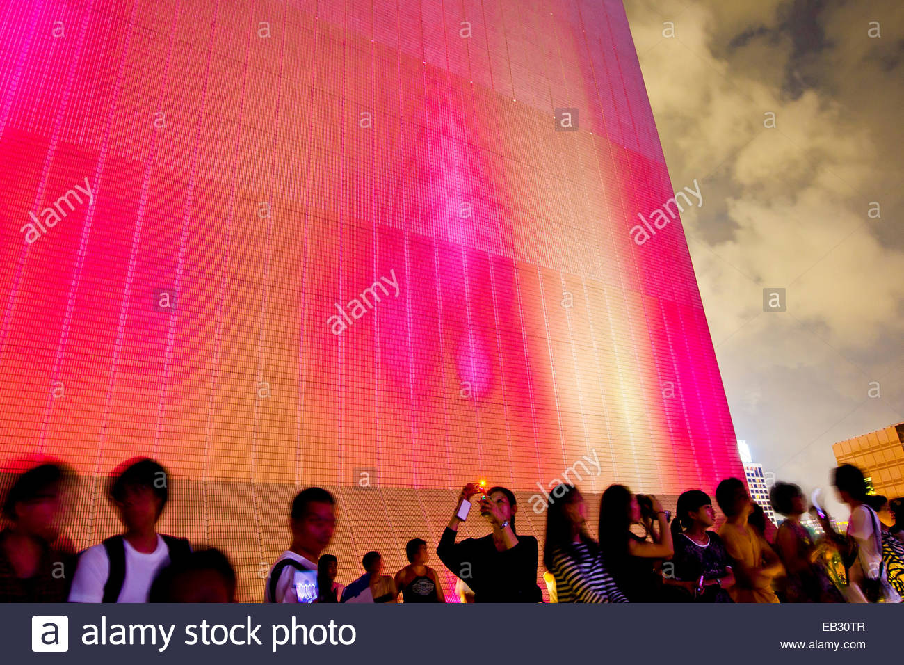 Colorful lights illuminate a building as people watch the Symphony of Lights laser and light show over the city Stock Photo