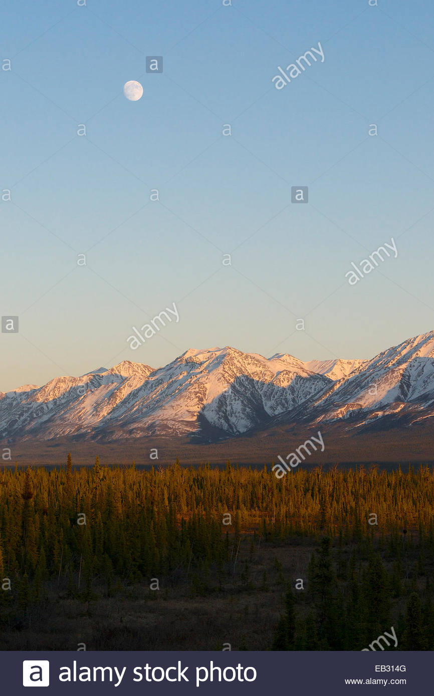 The moon rises over the mountains in the Yukon. - Stock Image