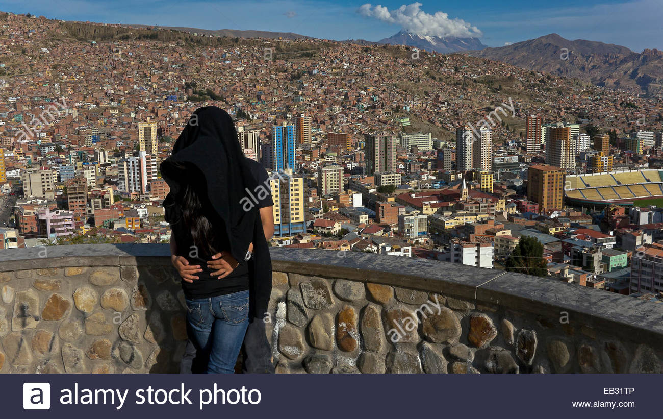 A couple embracing above the city of La Paz, which lies in a bowl between the Altiplano and the Cordillera Real, - Stock Image