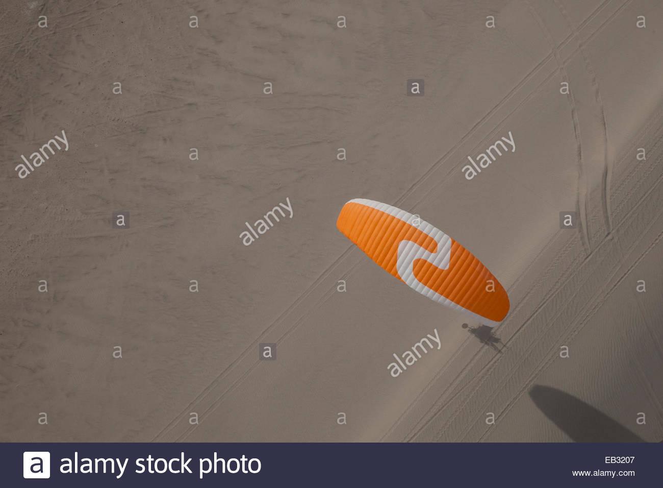 Flying a motorized paraglider over sand dunes in the Mojave Desert near Dumont Dunes. - Stock Image