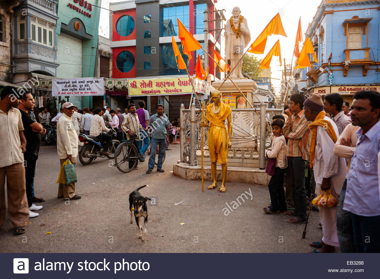 A street performer, Golden Gandhi, appears next to a statue of Mahatma Gandhi. - Stock Image
