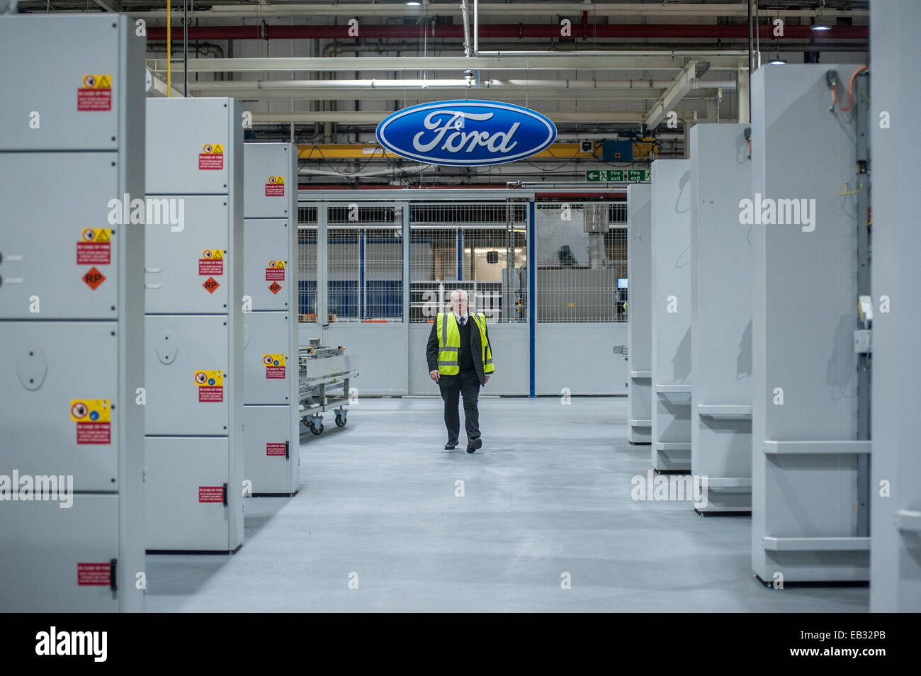London, UK. 25th November, 2014. An employee of Ford Motor Co Ltd in Dagenham walks next to the  the assembly line - Stock Image