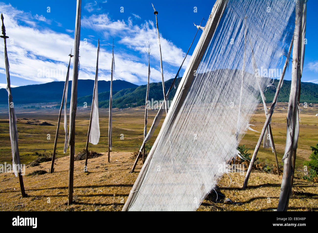 The translucent cloth of a prayer flag fluttering in the wind above a Himalaya wetland. - Stock Image