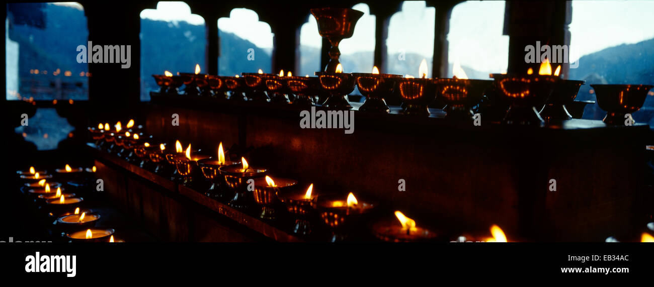 Tiered steps in a Himalayan Buddhist monastery lined with rows of butter lamps for prayers and worship. - Stock Image