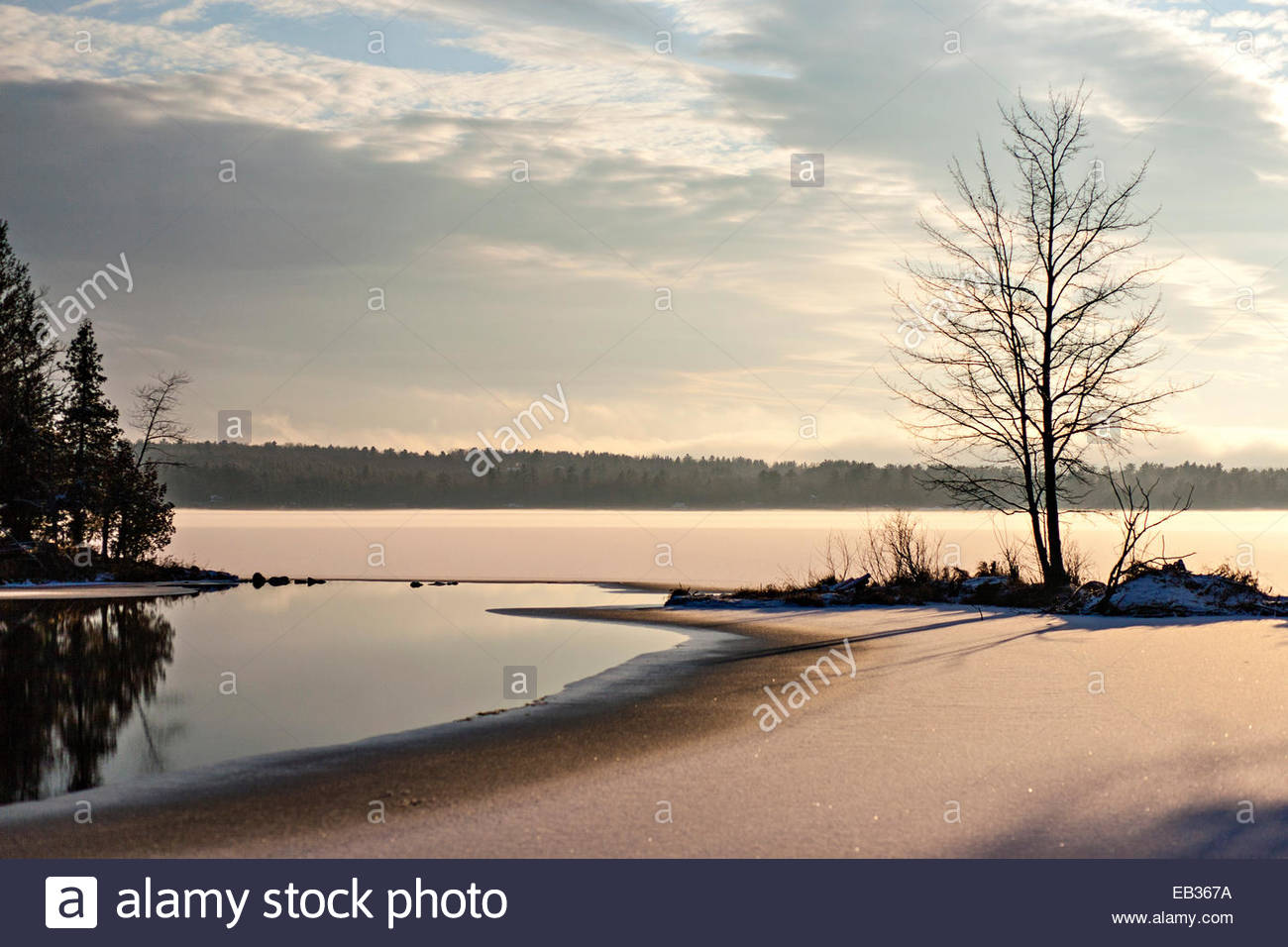 Sunset on a semi-frozen lake in Maine in early winter. - Stock Image