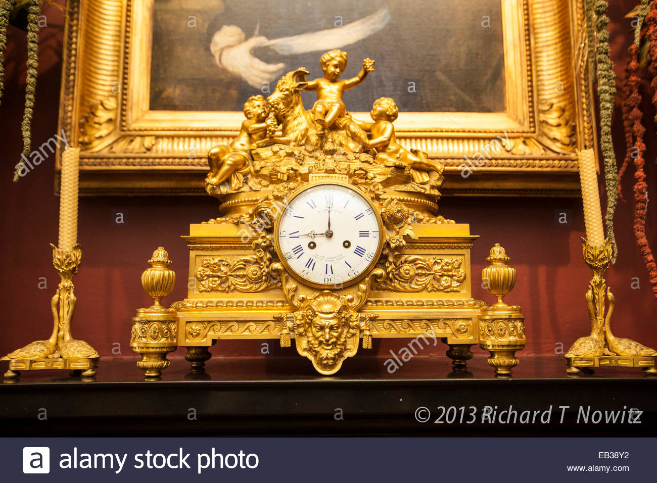 Antiques french clock that belonged to royalty decorates the mantle inside the historic house. Stock Photo