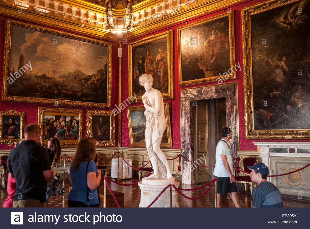 Tourists look at art in the Sala de Venue in the Palazzo Pitti. - Stock Image