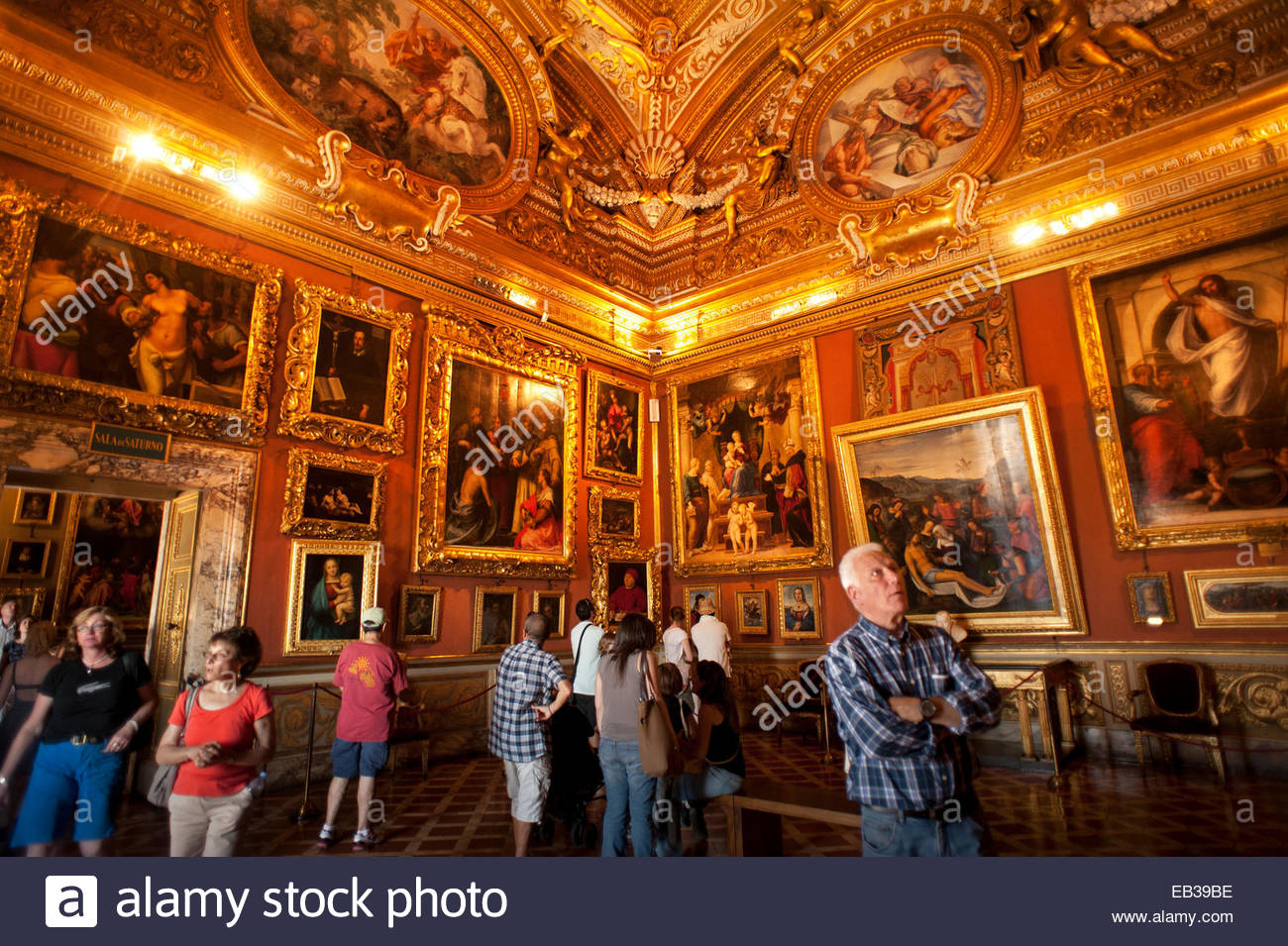 Tourists look at art in the Sala di Saturno in the Palazzo Pitti. - Stock Image