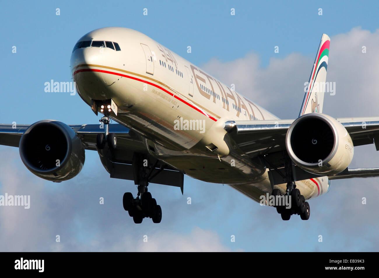 Etihad Airways Boeing 777-300 approaches runway 27L at London Heathrow airport. - Stock Image