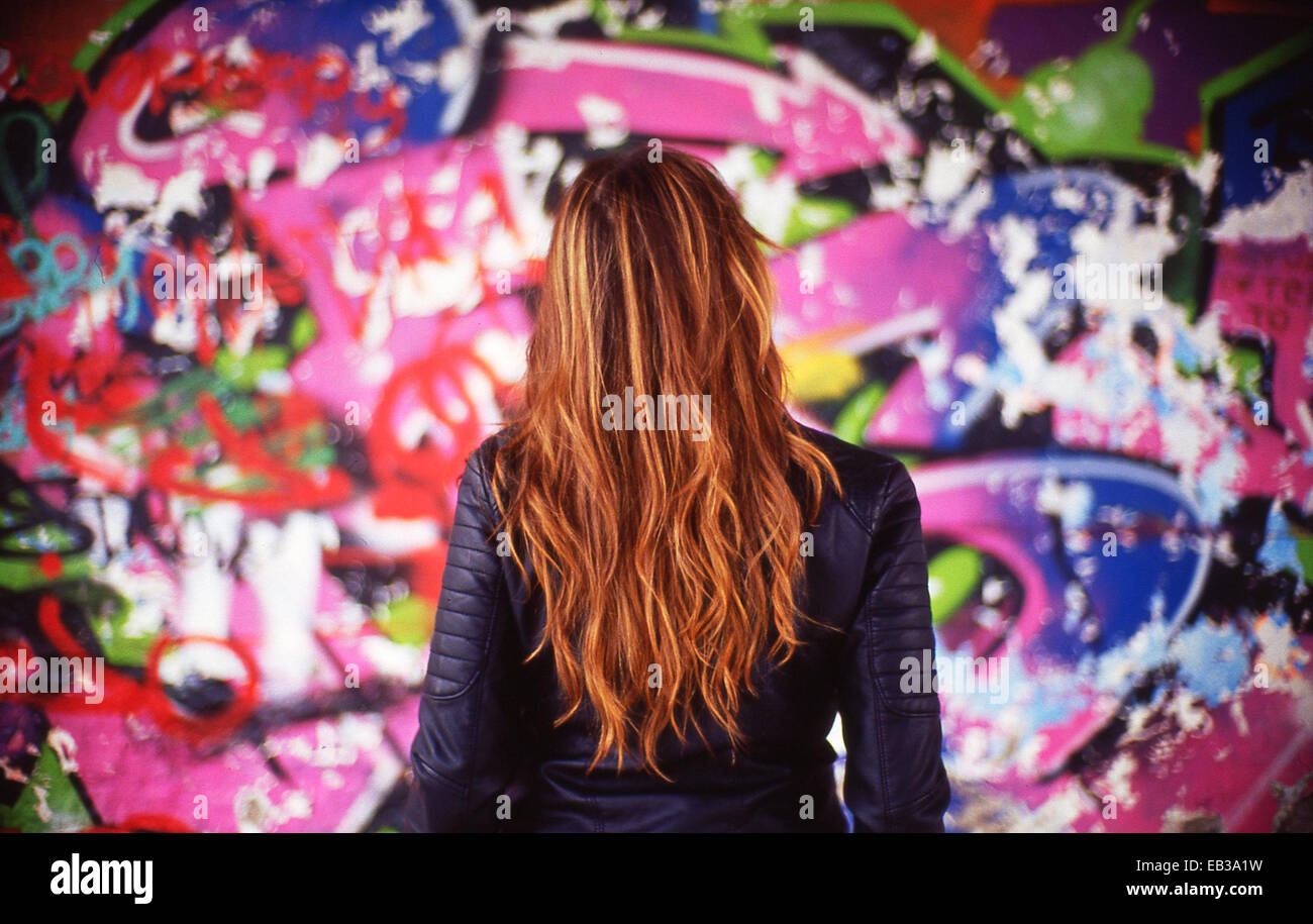 France, Rear view of young woman in front of colorful mural - Stock Image