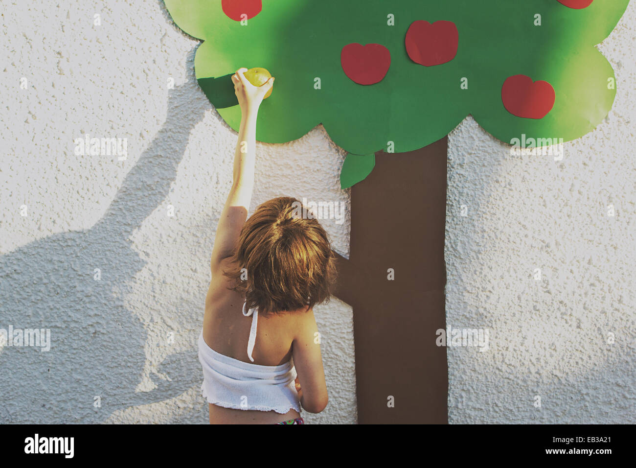 Girl pretending to pick an apple from conceptual tree - Stock Image