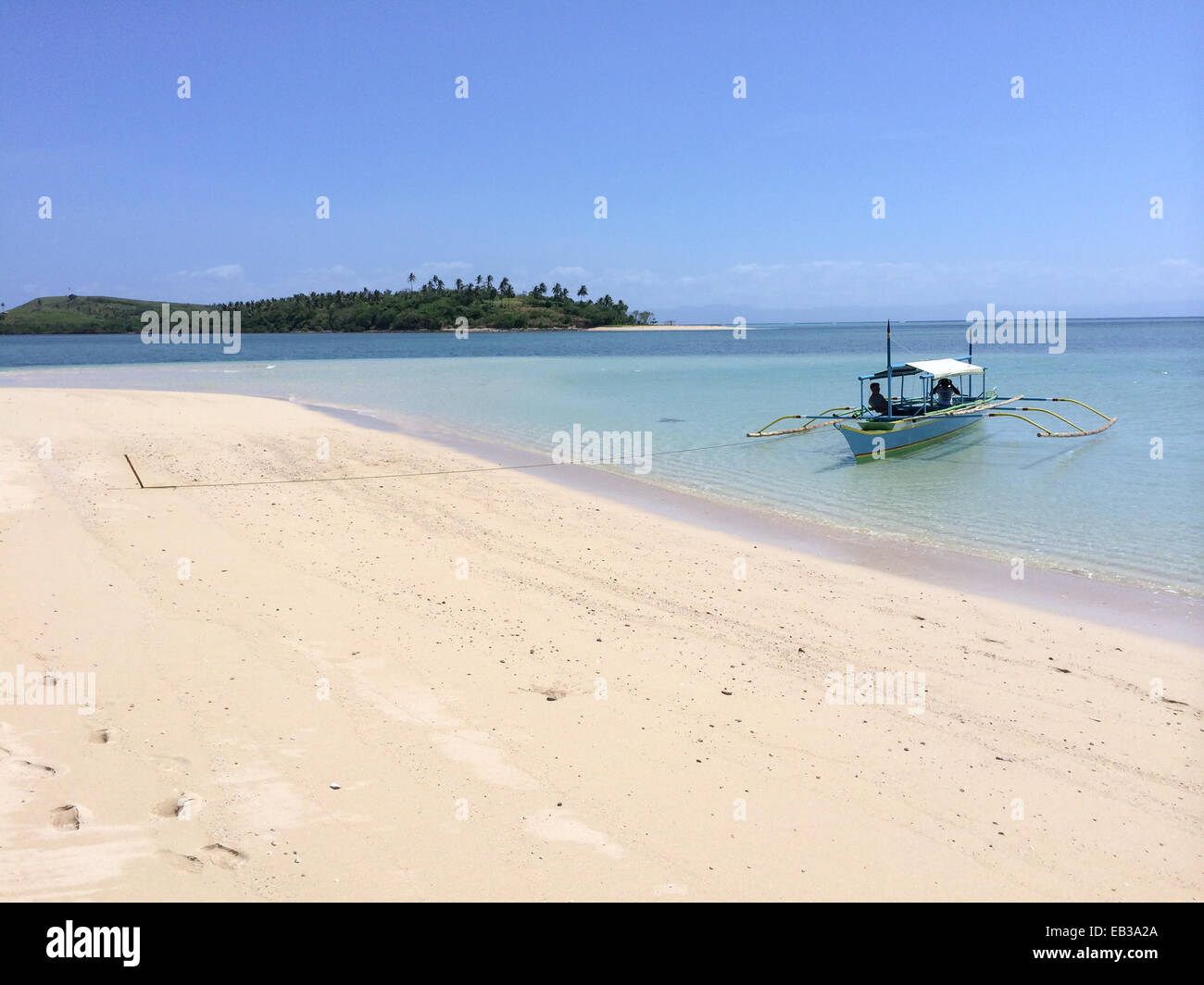 Philippines, Bicol Region, Camarines Sur, Caramoan, Bangka idling in shallow waters, tied to pole stuck into beach - Stock Image