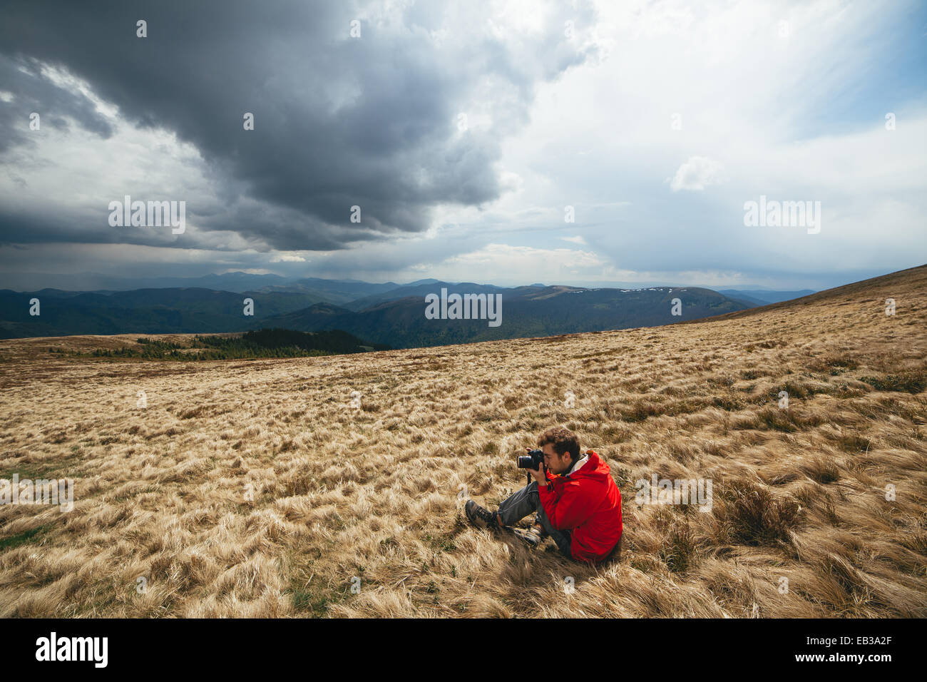 Young man wearing red sweater sitting withered grass photographing - Stock Image