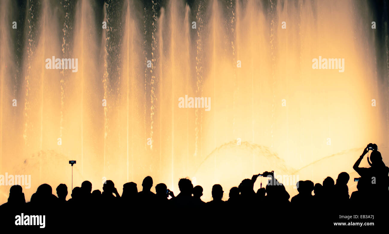 Silhouette of people in front of illuminated fountain - Stock Image