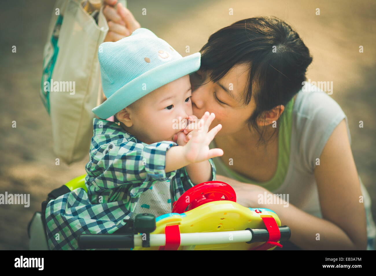Mother kissing son (6-11 months) - Stock Image