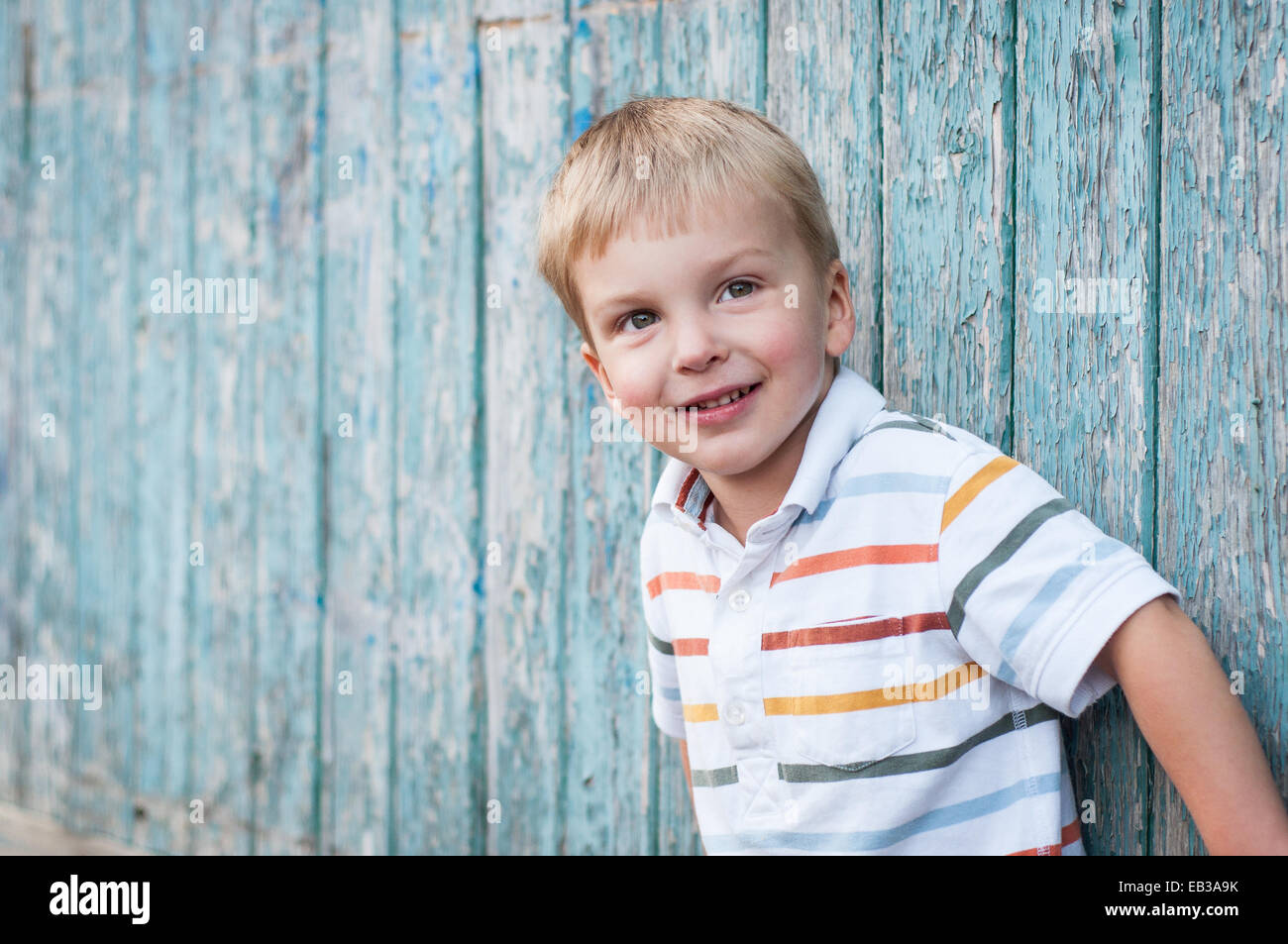 Portrait of boy leaning against  wooden wall - Stock Image