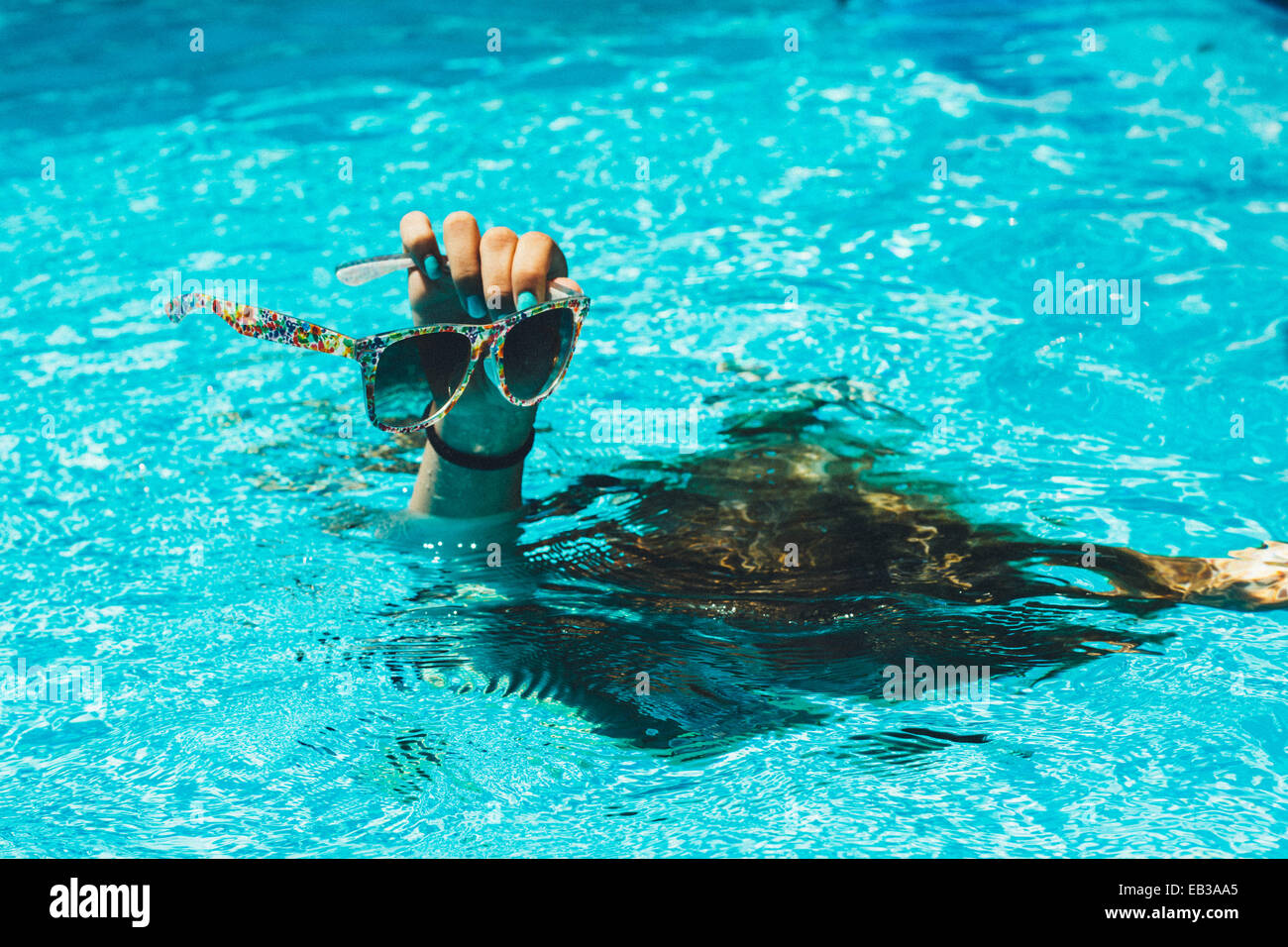 Hand with sunglasses sticking out of water - Stock Image