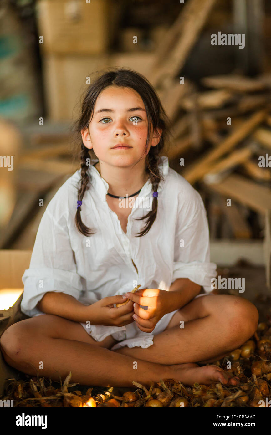 Portrait of a girl sitting cross-legged - Stock Image