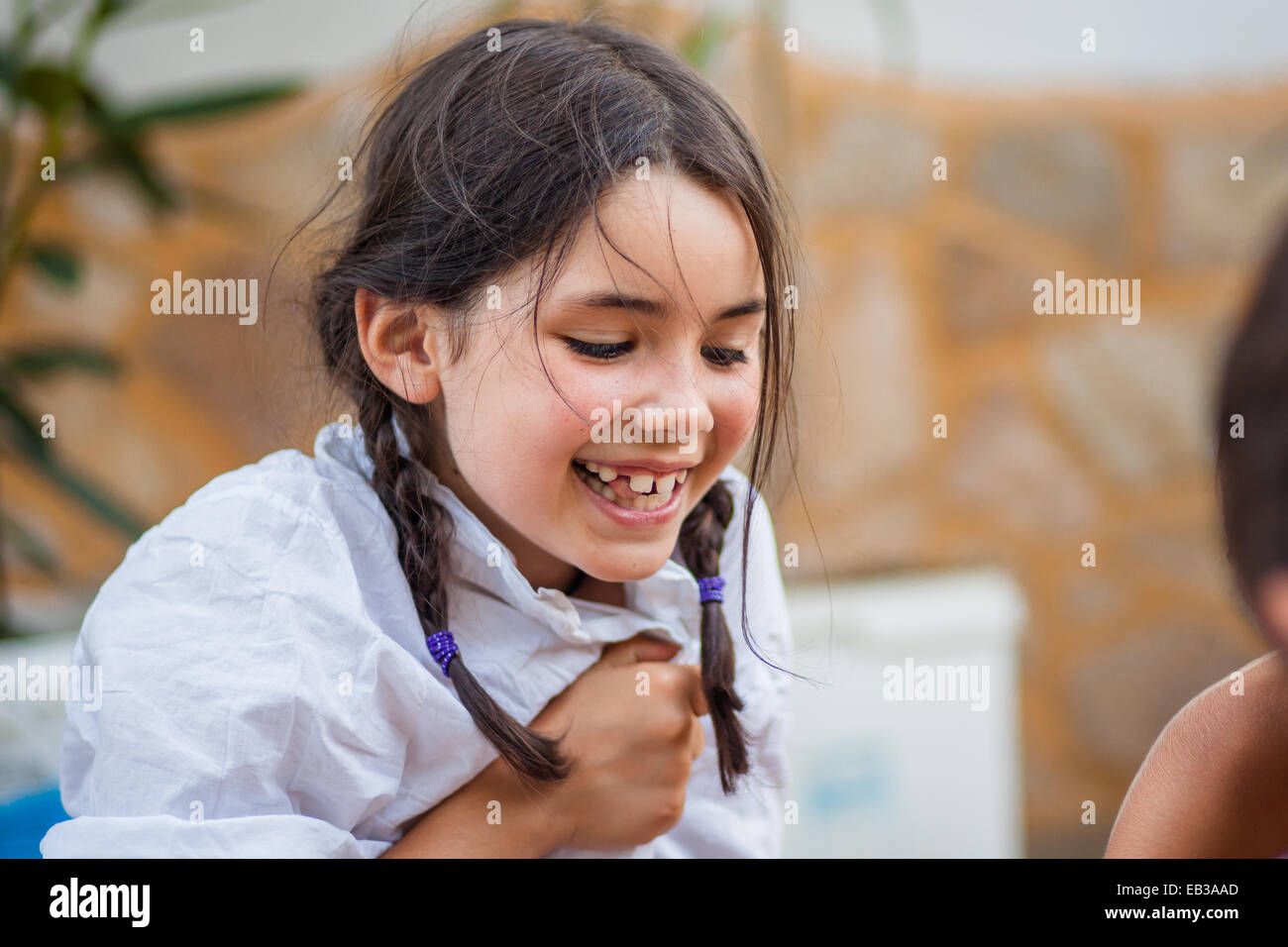 Little girl (6-7) with braids and white shirt laughing happily Stock Photo