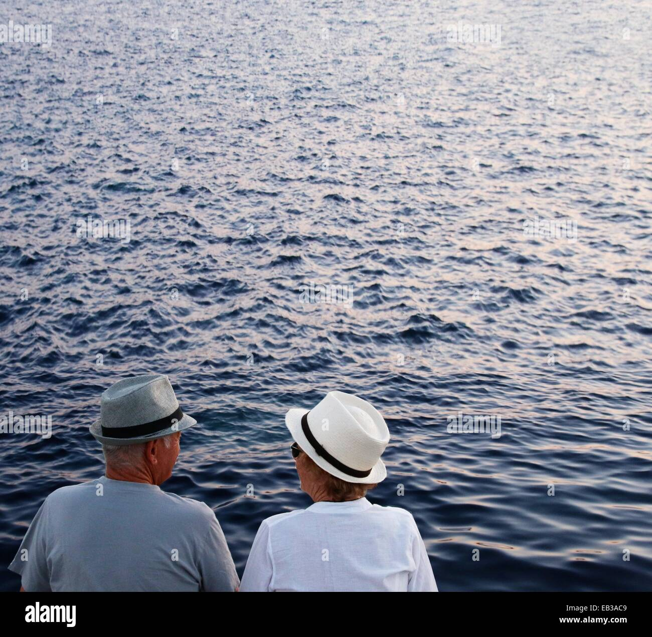 Italy, Sardinia, Couple with hats looking at sea - Stock Image