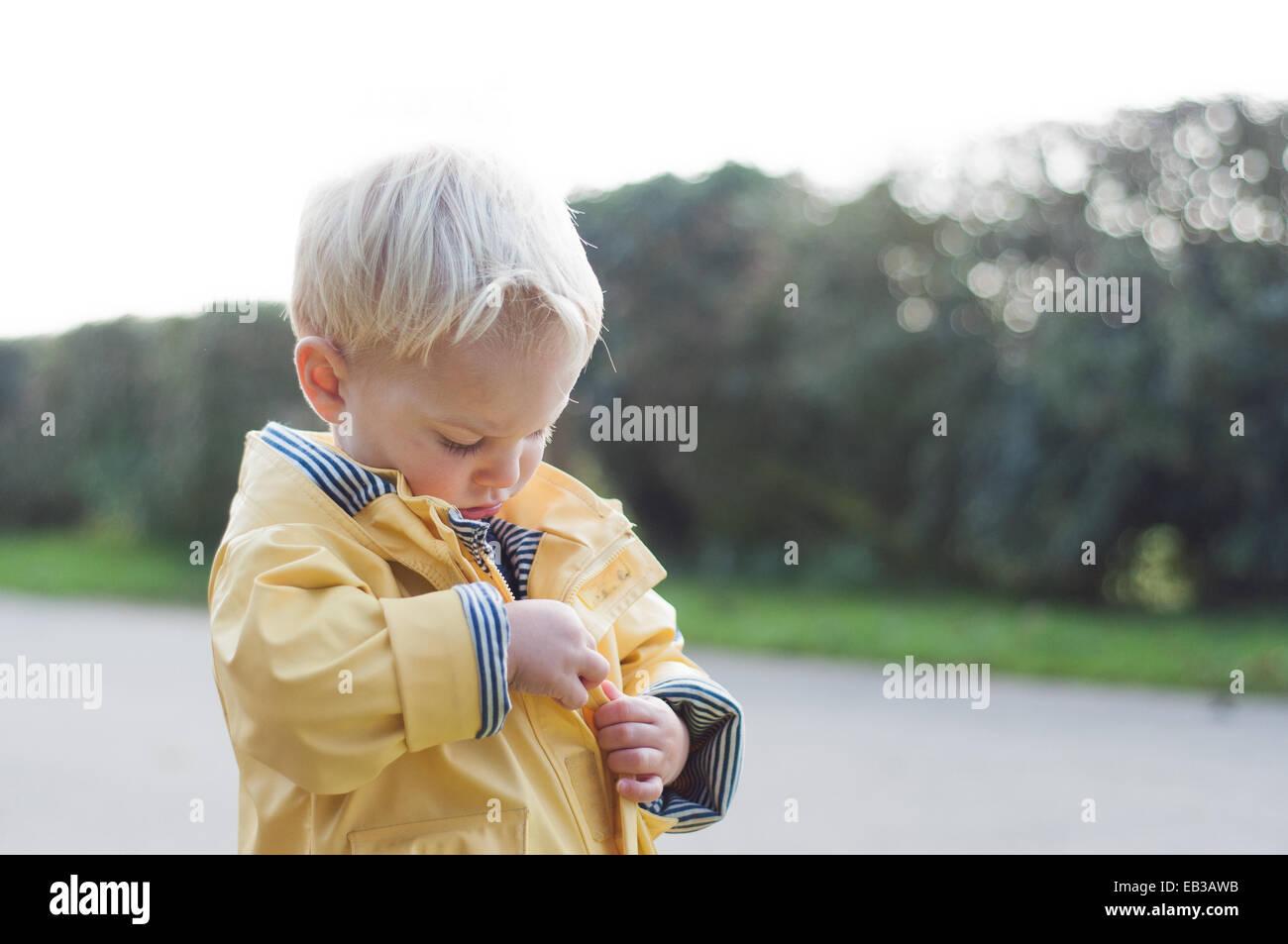 Boy zipping up rain coat - Stock Image