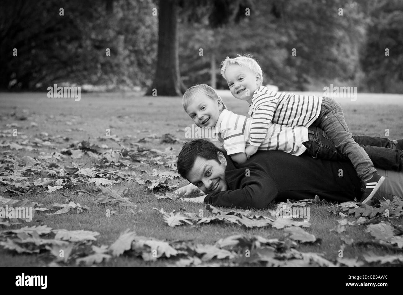 Portrait of father and sons lying on grass - Stock Image