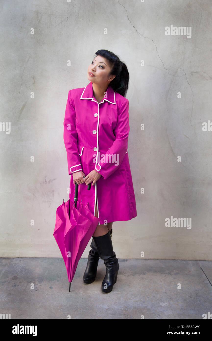 Woman wearing purple raincoat and holding umbrella - Stock Image