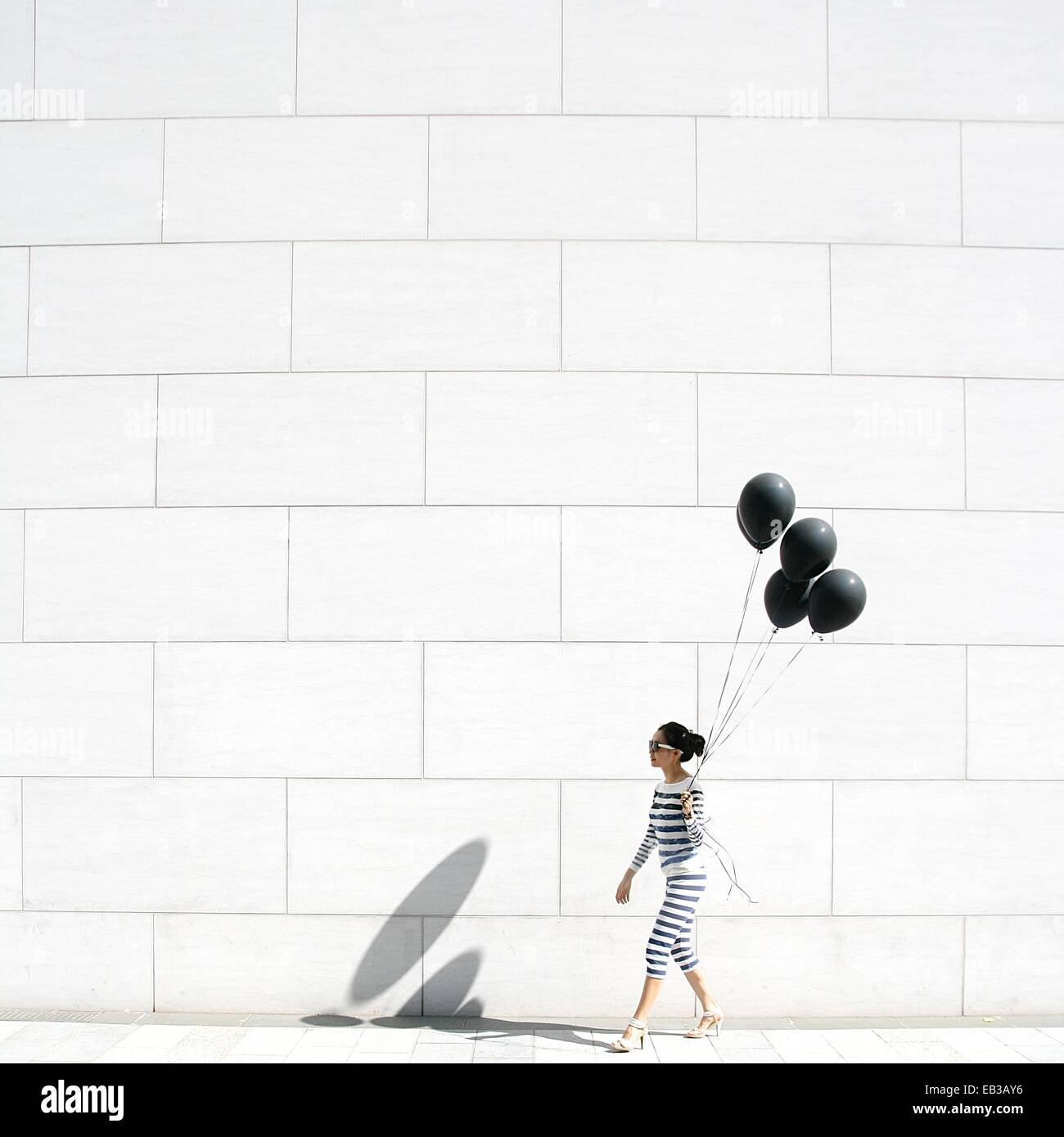 Woman walking with black balloons - Stock Image